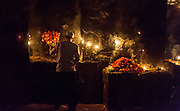 """19th November 2015, New Delhi, India. A man tends a shrine dedicated to Djinn worship in the ruins of Feroz Shah Kotla in New Delhi, India on the 19th November 2015<br /> <br /> PHOTOGRAPH BY AND COPYRIGHT OF SIMON DE TREY-WHITE a photographer in delhi<br /> + 91 98103 99809. Email: simon@simondetreywhite.com<br /> <br /> People have been coming to Firoz Shah Kotla to pray to and leave written notes and offerings for Djinns in the hopes of getting wishes granted since the late 1970's. Jinn, jann or djinn are supernatural creatures in Islamic mythology as well as pre-Islamic Arabian mythology. They are mentioned frequently in the Quran  and other Islamic texts and inhabit an unseen world called Djinnestan. In Islamic theology jinn are said to be creatures with free will, made from smokeless fire by Allah as humans were made of clay, among other things. According to the Quran, jinn have free will, and Iblīs abused this freedom in front of Allah by refusing to bow to Adam when Allah ordered angels and jinn to do so. For disobeying Allah, Iblīs was expelled from Paradise and called """"Shayṭān"""" (Satan).They are usually invisible to humans, but humans do appear clearly to jinn, as they can possess them. Like humans, jinn will also be judged on the Day of Judgment and will be sent to Paradise or Hell according to their deeds. Feroz Shah Tughlaq (r. 1351–88), the Sultan of Delhi, established the fortified city of Ferozabad in 1354, as the new capital of the Delhi Sultanate, and included in it the site of the present Feroz Shah Kotla. Kotla literally means fortress or citadel."""