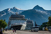 Cruise ships and the Chikat Range, seen in Skagway, Alaska, USA. Skagway was founded in 1897 on the Alaska Panhandle. Skagway's population of about 1150 people doubles in the summer tourist season to manage more than one million visitors per year. Half of Alaska's total visitors come via cruise ships. Klondike Gold Rush National Historical Park commemorates the late 1890s Gold Rush with three units in Municipality of Skagway Borough: Historic Skagway; the White Pass Trail; and Dyea Townsite and Chilkoot Trail. (A fourth unit is in Pioneer Square National Historic District in Seattle, Washington.)
