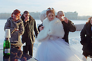St Petersburg, Russia, January 2003..Petersburgers make the most of the city's famous parks and waterways at any time of the year: a bridal party shivers by the River Neva in temperatures of minus 25 Celsius.