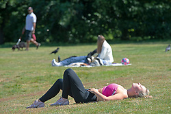 ©Licensed to London News Pictures 15/05/2020  <br /> Greenwich, UK. A female runner taking a break from exercising for a sunbathe. Warm sunny weather in Greenwich park, Greenwich, London as people get out of the house from coronavirus lockdown to exercise and enjoy more freedom to meet family and friends. Photo credit:Grant Falvey/LNP