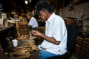 Hispanic men roll cigars in a workshop