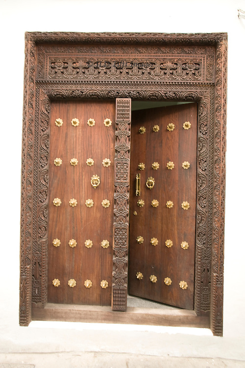 Stonetown wooden door studded with large headed brass nails.  Jams and architrave are delicately carved with ornamental themes.