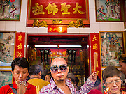 """19 FEBRUARY 2015 - BANGKOK, THAILAND: People pray at a shrine in Bangkok's Chinatown on Chinese New Year. 2015 is the Year of Goat in the Chinese zodiac. The Goat is the eighth sign in Chinese astrology and """"8"""" is considered to be a lucky number. It symbolizes wisdom, fortune and prosperity. Ethnic Chinese make up nearly 15% of the Thai population. Chinese New Year (also called Tet or Lunar New Year) is widely celebrated in Thailand, especially in urban areas that have large Chinese populations.    PHOTO BY JACK KURTZ"""
