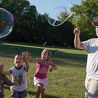 Children try to puck soap bubbles during a soap bubble day in a public park in Budapest, Hungary on August 19, 2012. ATTILA VOLGYI