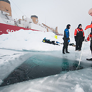 Shawn Harper holds a dive line for a fellow diver while the Polar Sea Icebreaker waits for their return. Arctic Ocean