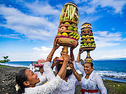 20 JULY 2016 - KUSAMBA, BALI, INDONESIA:  Balinese Hindu women gather for a procession to a nearby temple after a ceremony on Kusamba beach. Several hundred Balinese Hindus gathered on the beach in Kusamba, Bali, for a ceremony to honor the full moon. They prayed for more than hour and then community leaders threw an offering into the ocean.      PHOTO BY JACK KURTZ