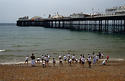 A class of schoolboys accompanied by their teachers play on the shingle at the water's edge in the south coast seaside town of Brighton. The East Pier is resplendent with amusement rides and attractions that populate its long structure, jutting out into the calm English Channel beyond which is the French coast further south. The children are still in their school shirts, shorts and ties but have taken off their shoes and socks to frolic and enjoy some precious fresh-air and the freedom that childhood brings. According to British legal requirements, schoolchildren on away day visits must have accompanying adults with a ratio of 1:xx though it appears this group's quota is less with two teachers per 28 boys.