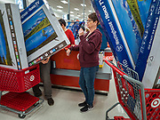 """28 NOVEMBER 2019 - ANKENY, IOWA: JULIE MALONE, a Target employee, checks out a customer who bought five 50 inch 4K HD televisions at the Target store in Ankeny, Iowa, Thursday evening. """"Black Friday"""" is the unofficial start of the Christmas holiday shopping season and has traditionally thought to be one of the busiest shopping days of the year. Brick and mortar retailers, like Target, are facing increased pressure from online retailers this year. Many retailers have started opening on Thanksgiving Day. Target stores across the country opened at 5PM on Thanksgiving to attract shoppers with early """"Black Friday"""" specials.    PHOTO BY JACK KURTZ"""