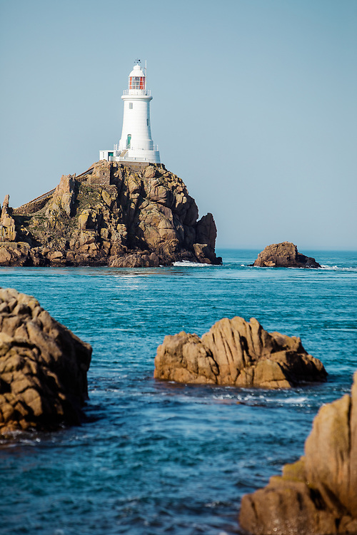 Corbiere lighthouse, a popular tourist destination and landmark in Jersey, Channel Islands, surrounded by calm blue water at high tide in summer
