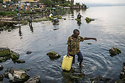 A boy fetches water directly from the Kivu Lake. If the residents come to the lake and fetch the water, they do not pay for the water and a worker from Solidarite will inject a dose of chlorine.