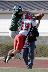 07 October 2006: Red Man Tom DeBaker and Titan Mrtin Ceisel go airborne for the same pass. The Titans of Illinois Wesleyan University started off strong with a touchdown on the 2nd play from scrimmage in the game.  The Titans led most of the way, but failed to maintain the lead in the 4th quarter giving up the decision of this CCIW conference game to the Red Men of Carthage by a score of 31 - 28. Action was at Wilder Field on the campus of Illinois Wesleyan University in Bloomington Illinois.<br />