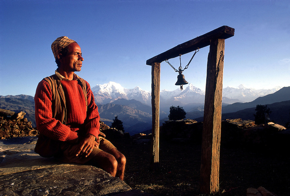 Gurkha L.Cpl Mairaj Thapa seen by the village prayer bell in his remote village. Nepal. 1969. Photographed by Terry Fincher