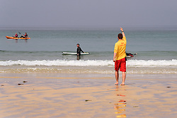 A RNLI Lifeguard instructing holidaymakers to move to a safer area on Fistral in Newquay, Cornwall.