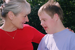 Mother with arm around teenage son with Downs Syndrome,