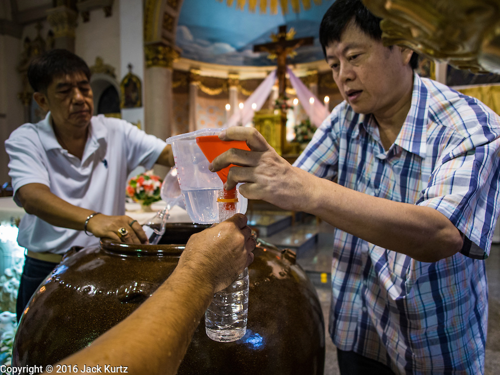 27 MARCH 2016 - BANGKOK, THAILAND: Men give out holy water after Easter services at Santa Cruz Church in Bangkok. Santa Cruz was one of the first Catholic churches established in Bangkok. It was built in the late 1700s by Portuguese soldiers allied with King Taksin the Great in his battles against the Burmese who invaded Thailand (then Siam). There are about 300,000 Catholics in Thailand, in 10 dioceses with 436 parishes. Easter marks the resurrection of Jesus after his crucifixion and is celebrated in Christian communities around the world.      PHOTO BY JACK KURTZ