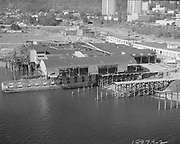 """Ackroyd-18973-2. """"LeBeck & Son. Aerials moving warehouse onto barge. August 2, 1974"""" (south Waterfront area south of the Hawthorne bridge. They are barging the entire 45,000 square feet Multnomah Plywood factory to its new home in St Helens.)"""