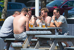 © Licensed to London News Pictures 14/06/2021. Folkestone, UK. Beer time before the football. The hot heatwave weather continues today in Kent as people enjoy the sun in Folkestone Harbour. Photo credit:Grant Falvey/LNP