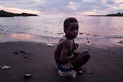 A young boy sits at the beach after playing football and swimming with friends at the Black Sand Beach in Lenakel.