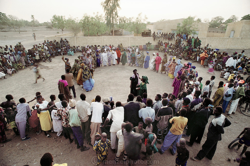 A gathering of townspeople in the village of Kouakourou, Mali during the Muslim holy month of Ramadan. Ramadan is the month for fasting, prayer, weddings, and other social activities. At the end of Ramadan, the entire village of Kouakourou, Mali, celebrated with a community dance. Material World Project.