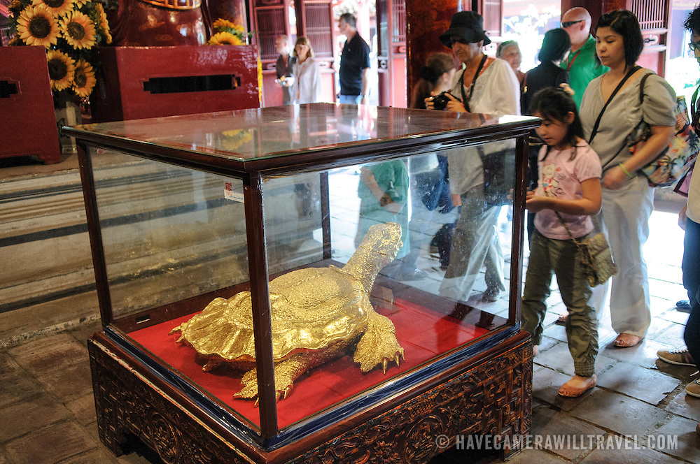 Visitors look at a display of a gold turtle, one Hanoi's sacred symbols, at the Temple of Literature in Hanoi. The temple was built in 1070 and is one of several temples in Vietnam which are dedicated to Confucius, sages and scholars.