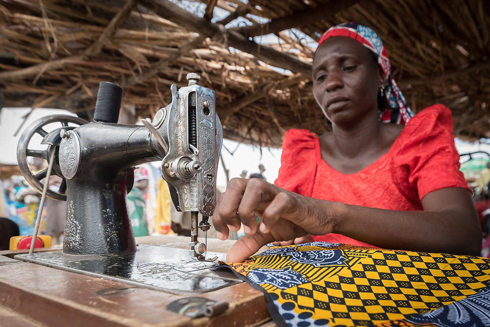 30 May 2019, Mokolo, Cameroon: 40-year-old Rhoda Joshua sews a skirt to be sold at the marketplace in Minawao. One of many Nigerian refugees in Minawao, Joshua uses her skill to make an income. She has been producing women's clothes for more than 10 years. Today is market day, and refugees and host communities alike gather to sell and buy goods in Minawao. The Minawao camp for Nigerian refugees, located in the Far North region of Cameroon, hosts some 58,000 refugees from North East Nigeria. The refugees are supported by the Lutheran World Federation, together with a range of partners.