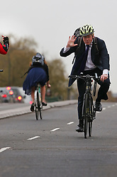 © Licensed to London News Pictures. 19/11/2015. London, UK.   London Mayor Boris Johnson receives the finger (L) from a fellow cyclist as he tries out the newly opened Cycle Superhighway 5  on Vauxhall Bridge. Dedicated cycle lanes are being installed throughout the capital.  Photo credit: Peter Macdiarmid/LNP