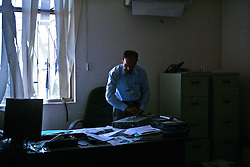 Muhammad Ahsan, a radio operator for the UN, picks up personal effects from a colleague's office while crews search for bodies at the Canal Hotel in Baghdad, Iraq on Aug. 21, 2003. Earlier in the week a cement truck packed with explosives detonated outside the offices of the UN headquarters in Baghdad, Iraq, killing 20 people and devastating the facility in an unprecedented suicide attack against the world body. At least 100 people were wounded.