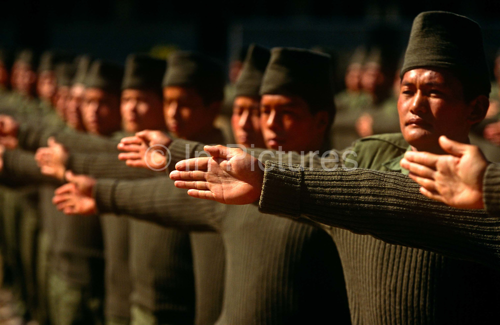Young Nepali boys adjust their spacing during a camp parade after recruitment to the British Gurkha Regiment. Trying for places in the Gurkha Regiment is part of a tough endurance series to find physically perfect specimens for British army infantry training. They will need to perform 25 straight-kneed sit-ups at a 45° slant both within 60 seconds to pass. 60,000 boys aged between 17-22 (or 25 for those educated enough to become clerks or communications specialists) report to designated recruiting stations in the hills each November, most living from altitudes ranging from 4,000-12,000 feet. After initial selection, 7,000 are accepted for further tests from which 700 are sent down here to Pokhara. Only 160 of the best boys succeed in the journey to the UK. The Gurkhas have been supplying youth for the British army since the Indian Mutiny of 1857.