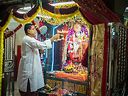 05 OCTOBER 2014 - GEORGE TOWN, PENANG, MALAYSIA:  A Hindu priest blesses the deity before a procession honoring Durga in George Town during the Navratri procession. Navratri is a festival dedicated to the worship of the Hindu deity Durga, the most popular incarnation of Devi and one of the main forms of the Goddess Shakti in the Hindu pantheon. The word Navaratri means 'nine nights' in Sanskrit, nava meaning nine and ratri meaning nights. During these nine nights and ten days, nine forms of Shakti/Devi are worshiped.   PHOTO BY JACK KURTZ