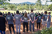 The ICS volunteers watch and listen to a song performed by the pupils of Endagikot school at the end of their ICS Raleigh SWASH (school water, sanitation and hygiene plan) project. Mbulu, Manyara district, Tanzania. Working in partnership with the Diocese of Mbulu Development Department (DMDD); part of Caritas Tanzania.