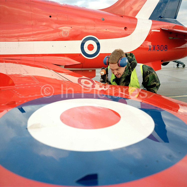 Junior Technician Brian Robb, an engineer with the elite 'Red Arrows', Britain's prestigious Royal Air Force aerobatic team, shines his torch inside the flaps of a Hawk jet aircraft checking for obstructions, RAF Scampton, Lincolnshire. Wearing ear defenders clasped to his head, J/Tech Robb peers into the wing assembly during a pre-flight inspection before the pilot emerges from for another winter training flight. Robb is a member of the team's support ground crew who outnumber the pilots 8:1 and without them, the Red Arrows couldn't fly.  Eleven trades are imported from some sixty that the RAF employs and teaches. Crouching by an RAF roundel emblem, he wears an army style green camouflage coat as protection over the biting Lincolnshire wind, and a fluorescent tabard required for any personnel working on the 'line', where the aircraft taxi to and park.