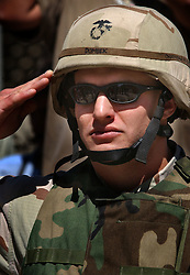 KABUL,AFGHANISTAN - SEPT. 11:  An American Marine salutes during the unveiling of a plaque where remains of the World Trade Center were laid as a symbolic gesture for those that died in the attack on the World Trade Center one year ago at the United States Embassy in Kabul, Afghanistan September 11,2002 . (Photo by Ami Vitale/Getty Images)