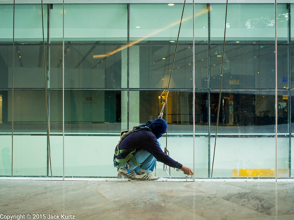 08 JULY 2015 - BANGKOK, THAILAND: A worker puts in a window in EmQuartier, a new high end shopping mall in Bangkok. EmQuartier is at the BTS Phrom Phong stop on the skytrain system.     PHOTO BY JACK KURTZ