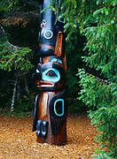 """Gaanaxadi/Raven Pole carved by Nathan Jackson and Steve Brown in 1983.  The original pole, either a crest pole or a legend pole depicting """"Raven and the Whale"""", was donated to John Brady in 1903 by Chief Gunyah of the Tlingit village of Tuxekan. This reproduction of the original pole resides in Sitka spruce forest, Sitka National Historic Park, Baranof Island, Southeast Alaska."""