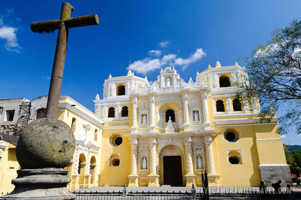 Christian iron cross and the distinctive  and ornate yellow and white exterior of the Iglesia y Convento de Nuestra Senora de la Merced in downtown Antigua, Guatemala.