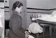 newborn baby being weighted by an at home visiting nurse 1960s