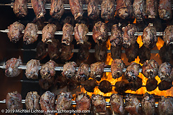 A flaming rotisserie cooks up some of the great food available at Motor Bike Expo. Verona, Italy. Saturday January 20, 2018. Photography ©2018 Michael Lichter.