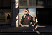 With a further 154 UK covid deaths reported in the last 24hrs, bringing the total to 43,081 victims during the Coronavirus pandemic, the easing of government lockdown restrictions for the re-opening of shops continues and a lady walks past a billboard for Canada Goose on Little Argyll Street, on 24th June, in London, England.