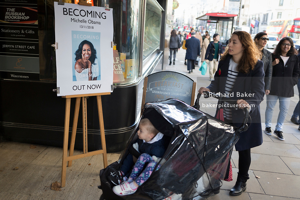 Outside Waterstones in Piccadilly, a mother passes a publicity board for the eagerly-anticipated bestselling title, 'Becoming' by the former First Lady of the United States, Michelle Obama, before her publicity tour of the UK, on 13th November 2018, in London, England.