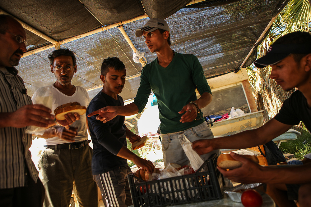 A Palestinian refugee, second to the right, hands out free meals, received from a greek NGO, to Syrian refugees at the Hotel Captain Elias in Kos, Greece on July 2, 2015. Migrants and refugees are each handed one ticket that is good for one small meal every afternoon by a greek NGO. Migrants and refugees claim that the food is two to three days old when they receive it. Many migrants and refugees purchase extra food in the city center because the free meal provided is not sufficient.