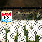 A no trespassing sign hangs on a fence around Arlington Cemetery.
