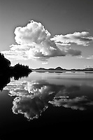 White cumulus clouds are reflected in the still water of Lake Kennedey near Tofino, Vancouver Island, BC Canada.<br /> Trees are silhouetted in black to the left and a range of mountains is seen in the distant horizon.