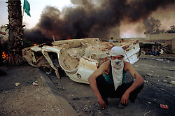 Palestinians hide behind burning cars as protests flared again near the West Bank town of Ramallah Wednesday, October 11, 2000.  (Photo by Ami Vitale)