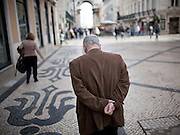 A man walks thoughtful at Rua Augusata, downtown Lisbon.This photograph is part of a body of work about Lisbon, feelings, affections and loneliness. Is about a city depressed by the crisis, but even so, tolerant and cosmopolitan. This part of Lisbon, the old town near the river Tejo (Tagus), with his deep character, where local people meets foreigners and alternative ways of life mixes with shamefaced poverty, is sublime by its peculiar light.