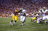1 September 2007: Tailback #13 Stafon Johnson pushes off Stanley Frankes during the USC Trojans college football team defeated the Idaho Vandals 38-10 at the Los Angeles Memorial Coliseum in CA.  NCAA Pac-10 #1 ranked team first game of the season. Johnson is wearing a special eye patch dedicated to Big Dad, his deceased grandfather this season.