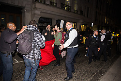 London, UK. 12th February, 2019. A police officer pushes members of grassroots trade union United Voices of the World protesting outside the Gadson Club in Pall Mall on the occasion of a reception with Justice Secretary David Gauke against his refusal to negotiate with the trade union over their demands for the London Living Wage, annual leave and sick pay for outsourced cleaners, security guards and receptionists working at the Ministry of Justice, all of whom have been on strike for varying periods recently. The Gadson Club is the official alumni club for the Oxford University Conservative Association.