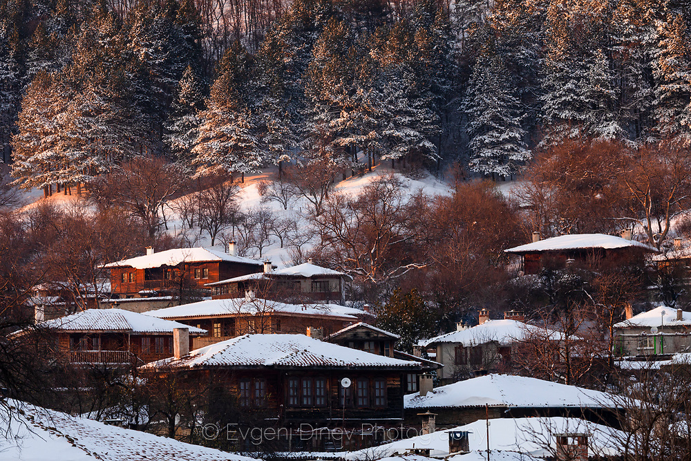 Old bulgarian village with traditional wooden houses at winter time