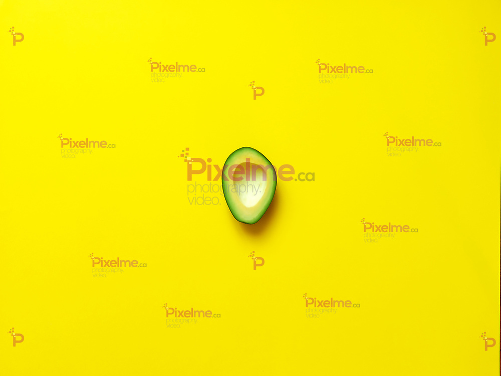 Avocado without seed isolated in yellow background viewed from above - flatlay look