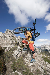 Mountain biker carries his bike on shoulder and walking uphill, Tirol, Austria