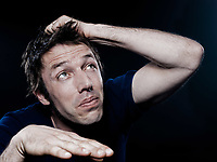 studio portrait on black background of a funny expressive caucasian man looking up scared